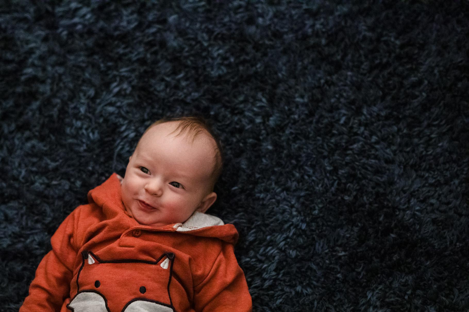 Baby boy wearing a fox jumper on a furry rug