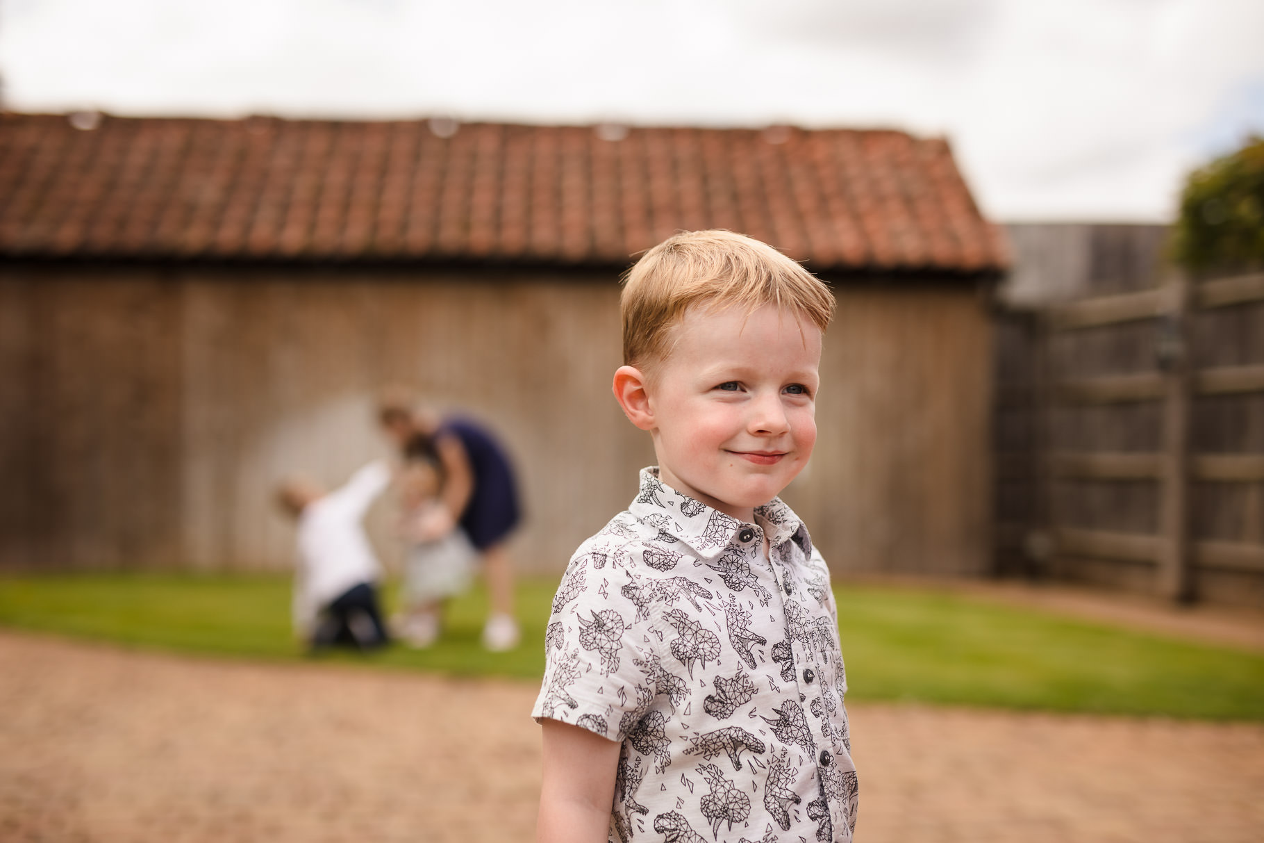Boy smiling with children playing in the background