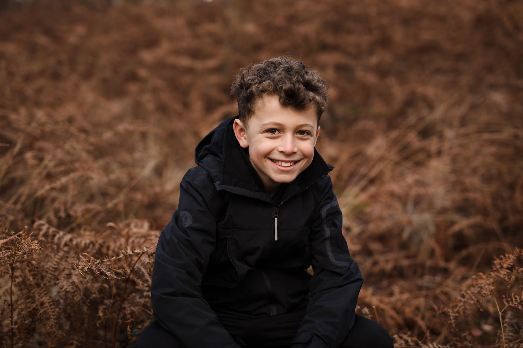 Boy with curly hair sitting in ferns at Moors Valley Country Park Bournemouth