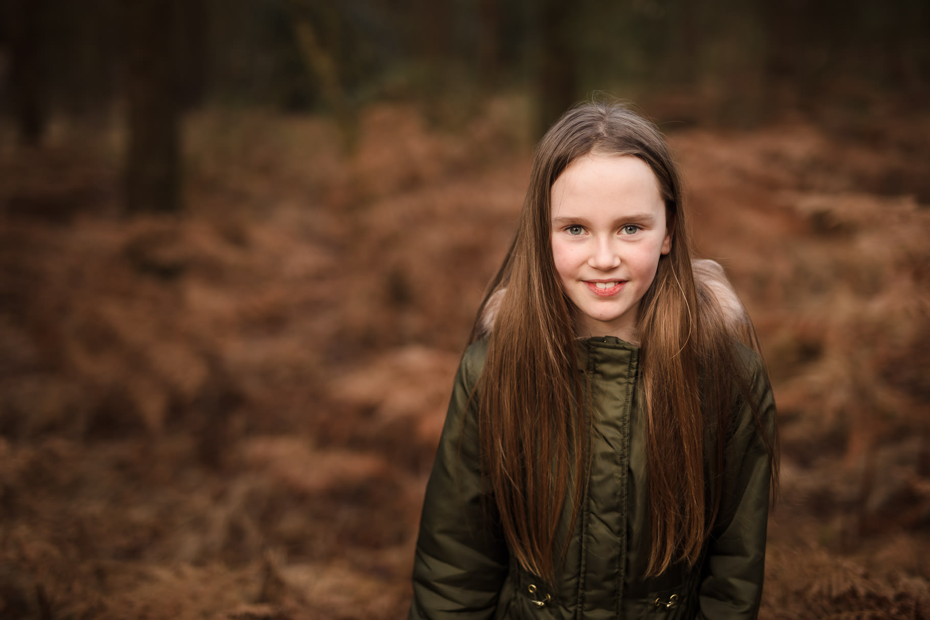Portrait girl in khaki coat surrounded by ferns at Moors Valley Country Park Ringwood