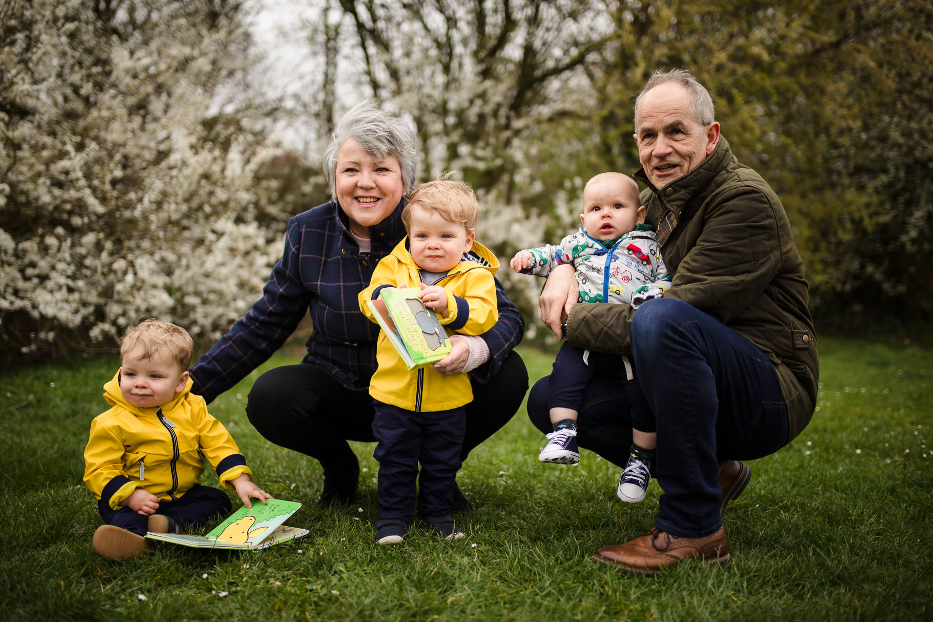 Portrait of grandparents with grandchildren outside in front of blossom at Chalfont Park Play Area Earley