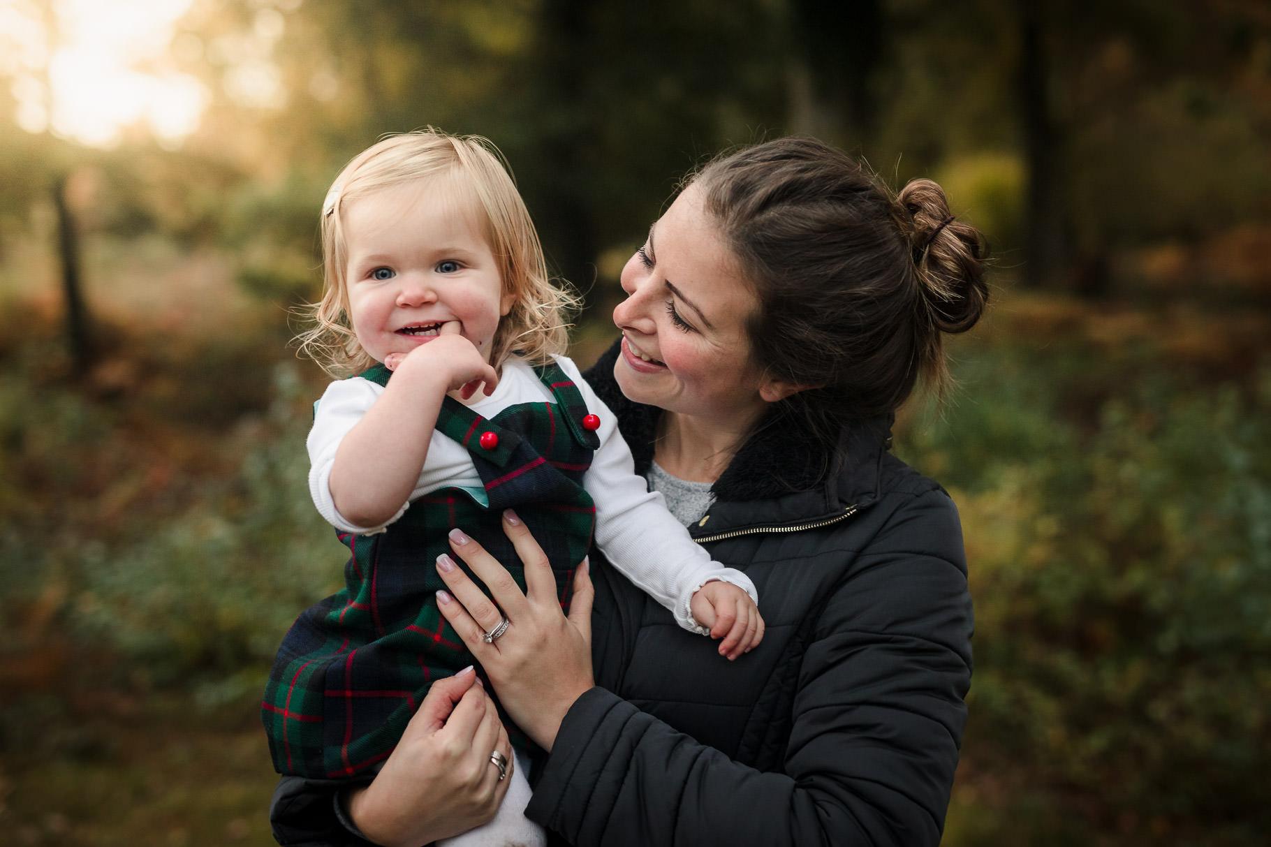 Mum smiling holding blonde girl outside at Burnham Beeches