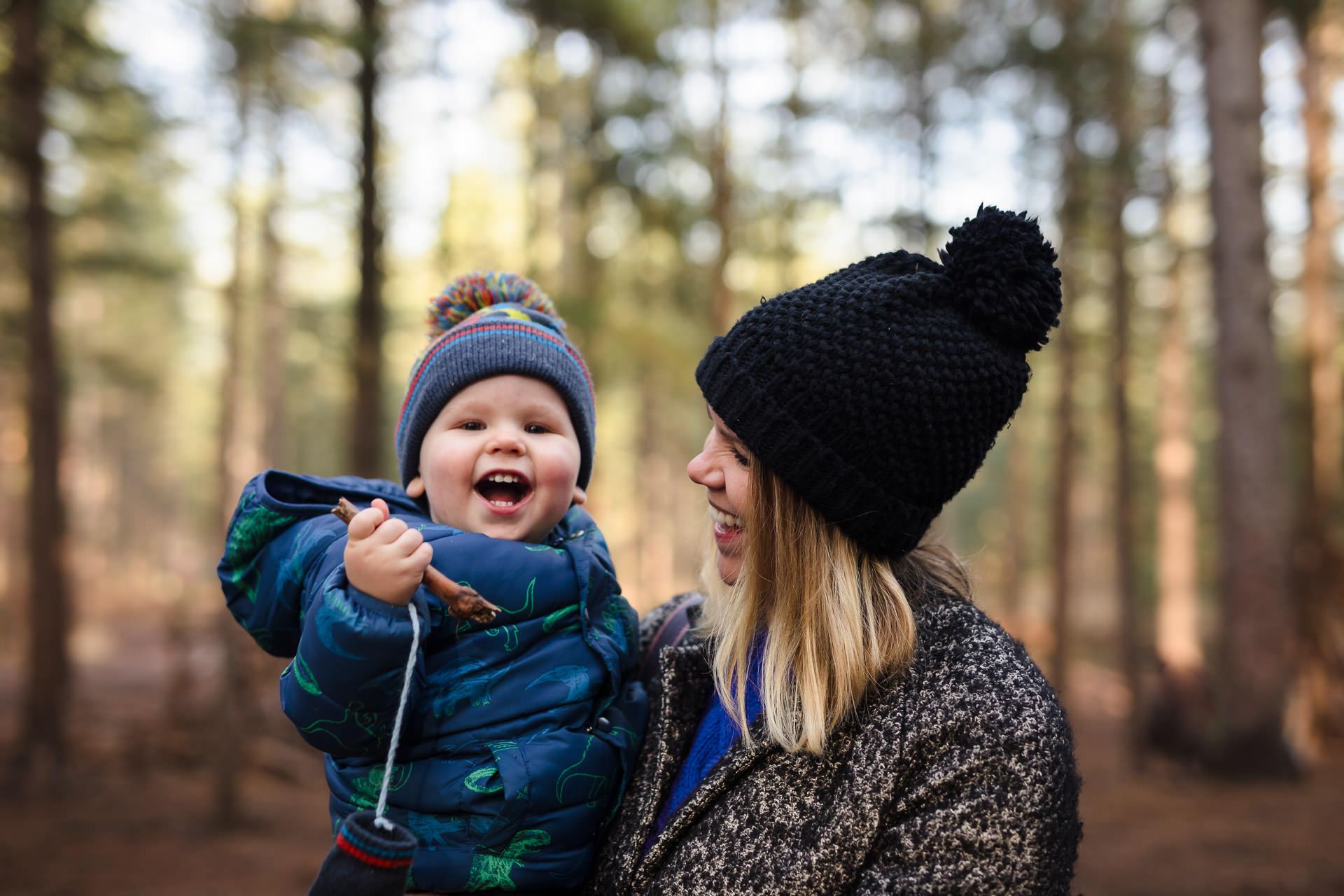Toddler and mum wearing bobble hats laughing at Moors Valley Country Park and Forest
