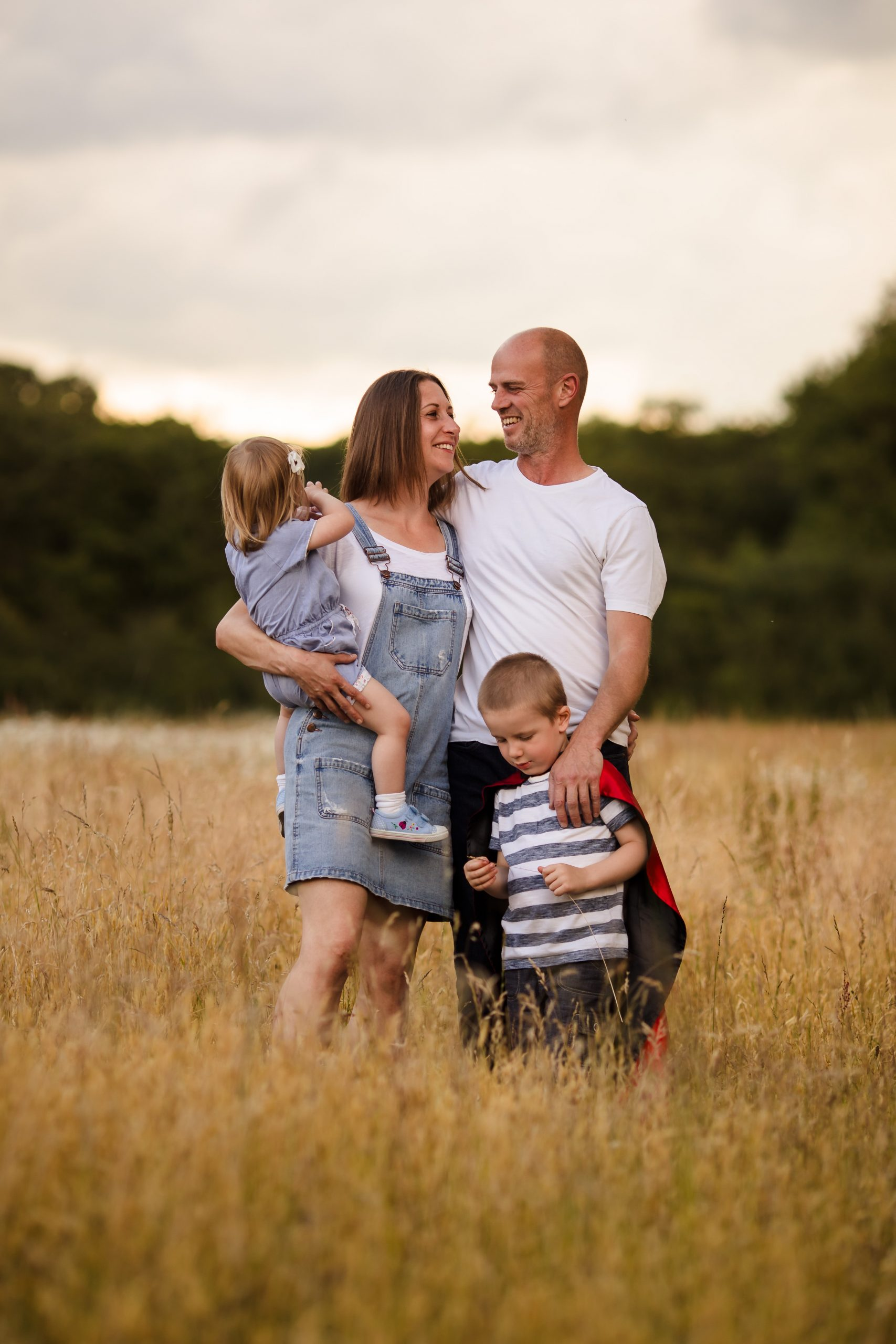 Family of four standing in a field of long grass