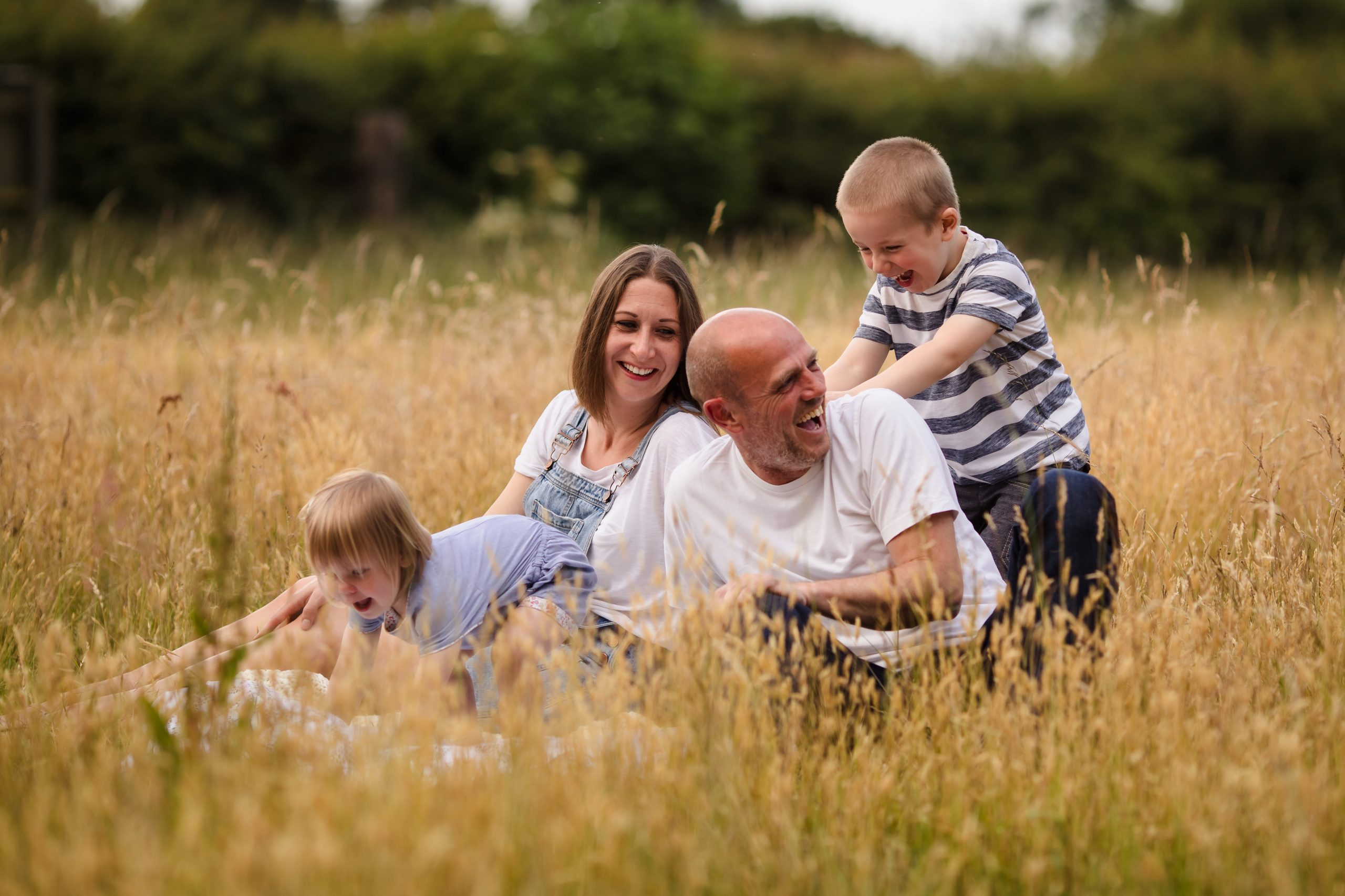 Family of four sat in a field laughing on an outdoor family photoshoot