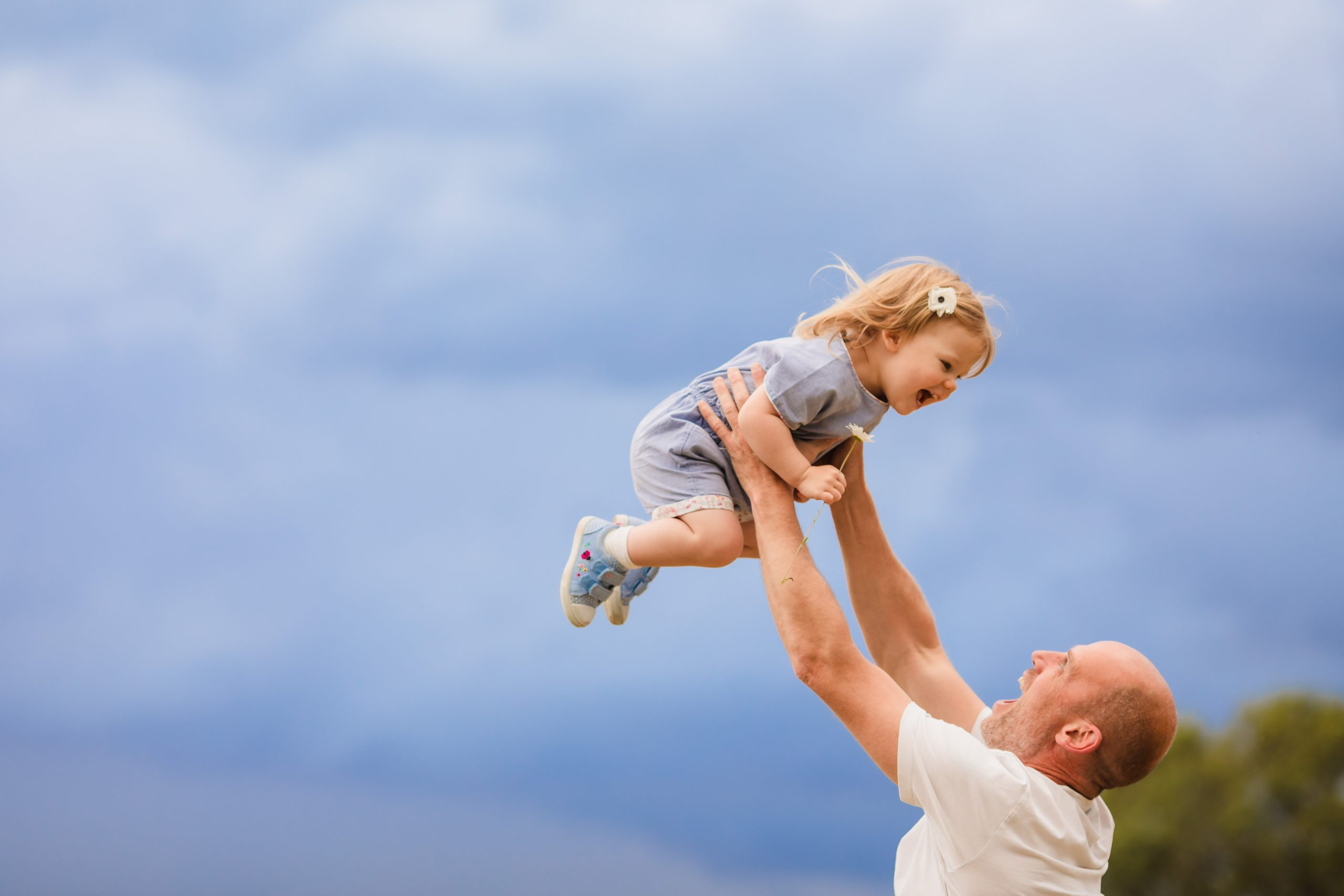 Girl holding daisy while dad throws her in the air