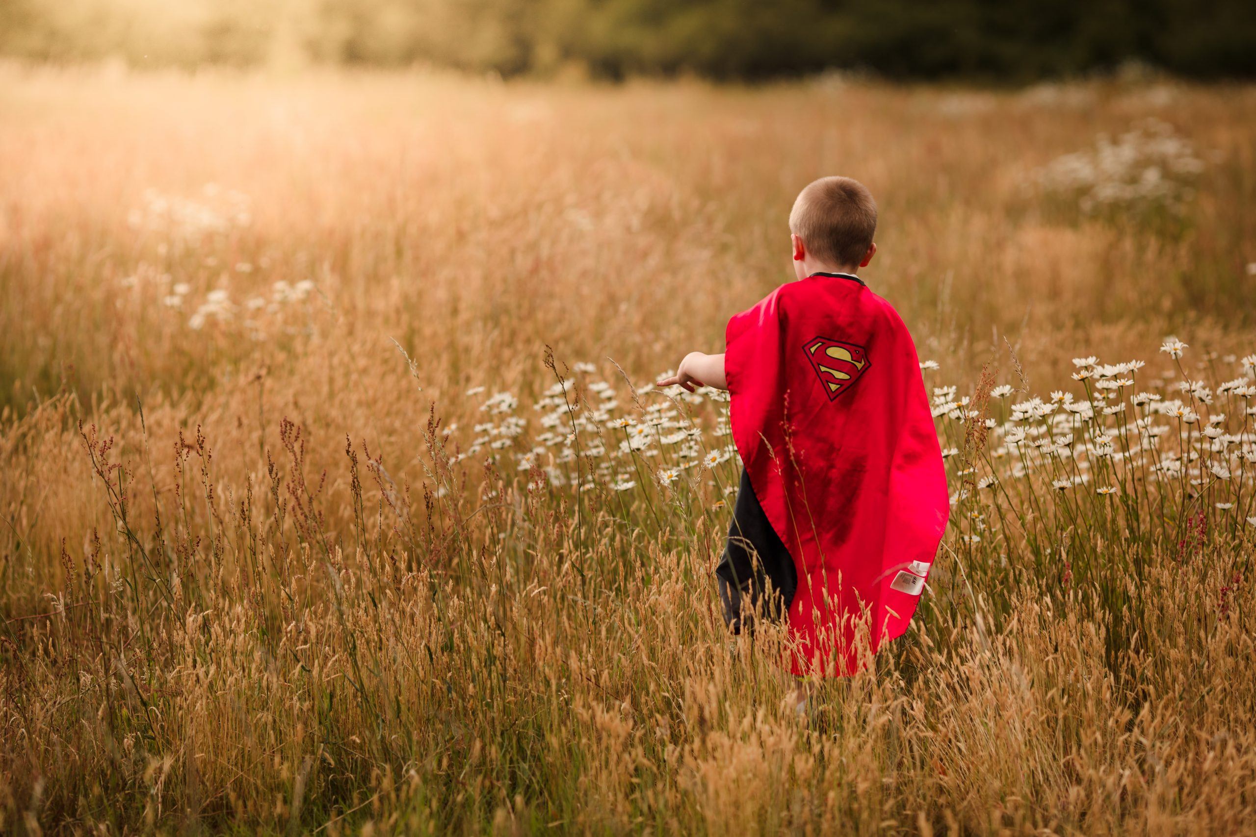 Boy wearing a cape running through a field on a Reading photography photo shoot