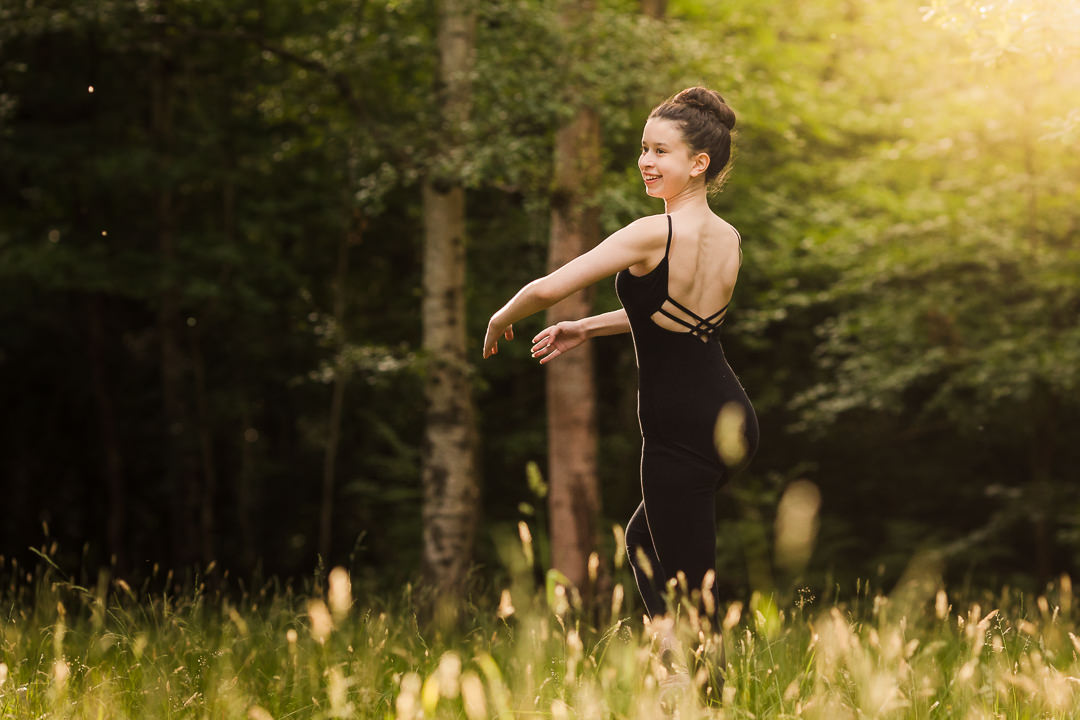Girl in strappy back leotard at an outdoor dance photo shoot at Burnham Beeches at sunset