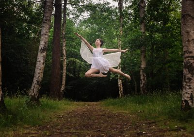 Girl wearing fairy wings jumping at an outdoor photo shoot
