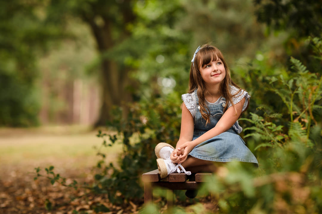 girl with a blue bow in her hair sat on bench at a park