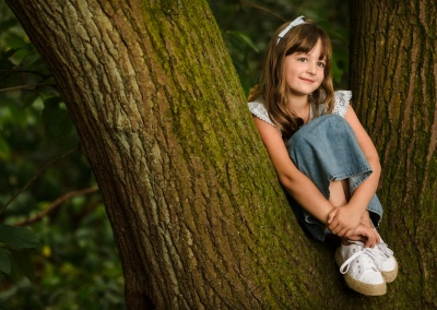 Girl sat on a tree with a blue bow