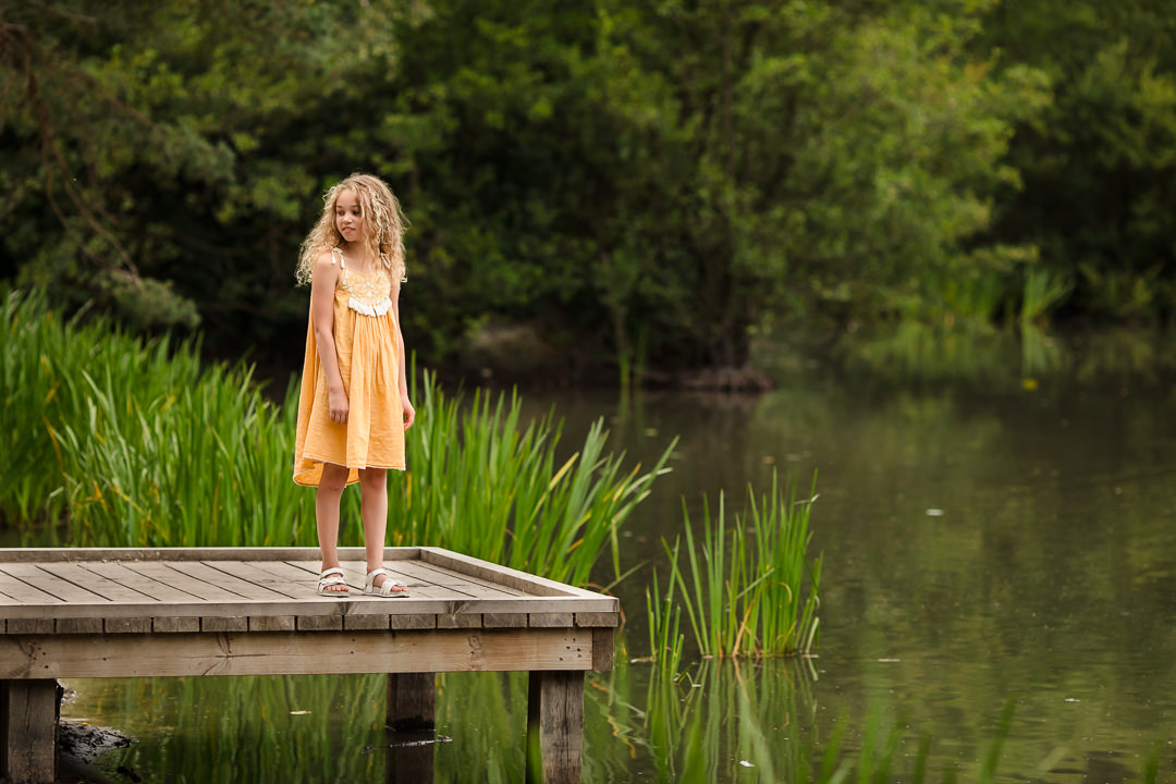 Girl in yellow dress standing on jetty at Lightwater Country Park Surrey