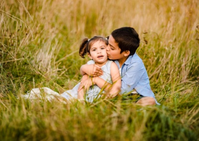 Children sat in a grass field hugging and kissing on a sibling photo shoot
