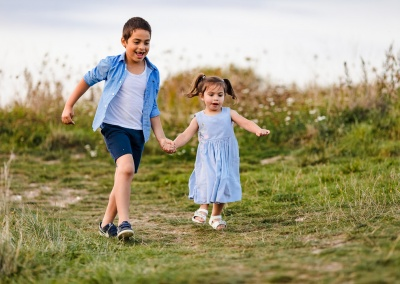 Children running down a hill on a sibling photo shoot at Lower Earley
