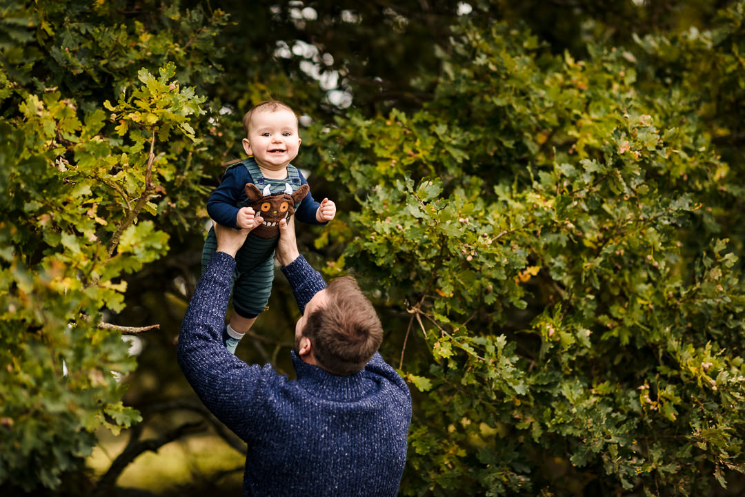 Dad throwing son in the air at Sulham Woods