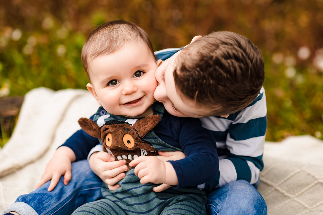 Brother cuddling baby brother on an autumn photo shoot near Sulham
