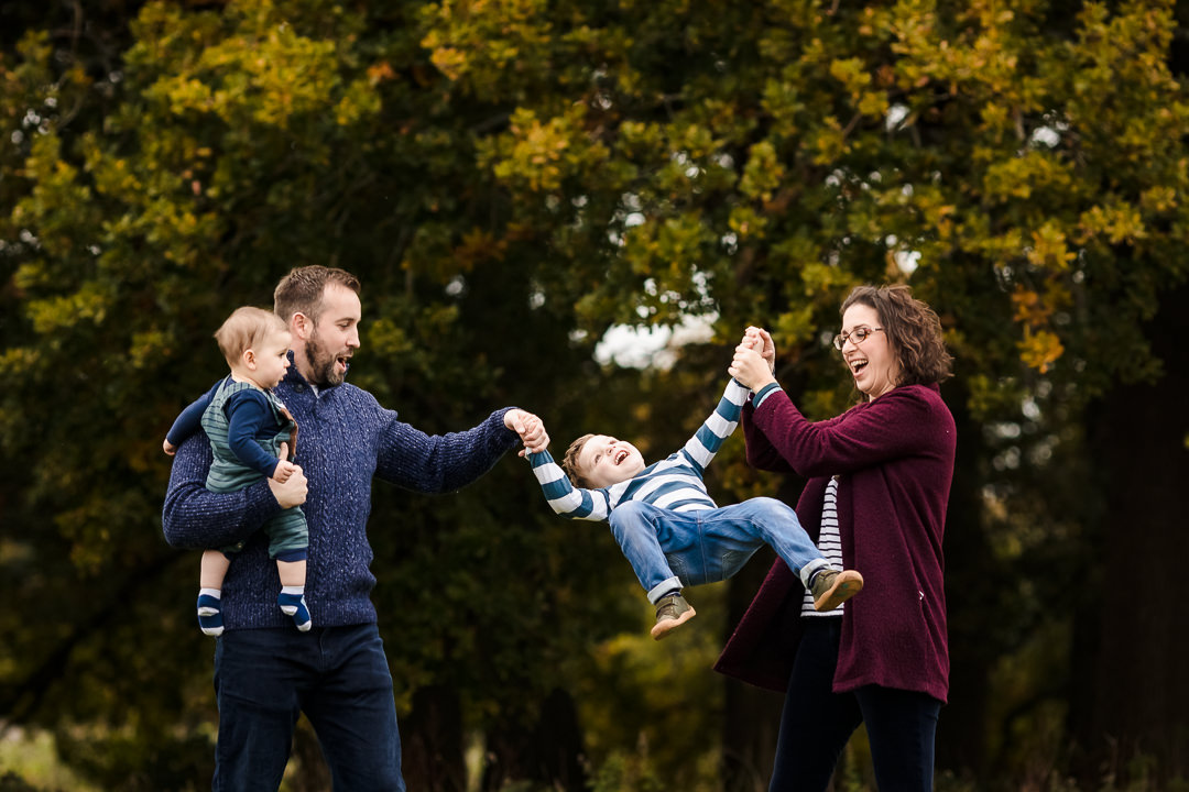 Family swinging boy in the air on an autumn photo shoot near Sulham