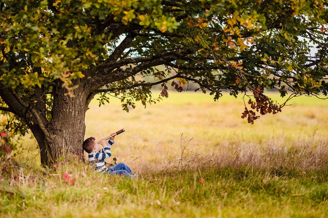 Boy sat under an oak tree on an autumn photo shoot near Sulham