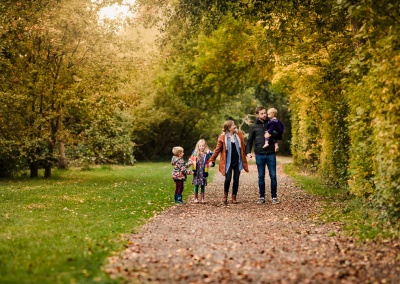 Family holding hands on an autumn photo shoot at Dinton Pastures Country Park