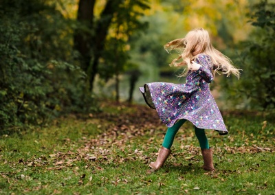 Girl spinning in a purple dress on an autumn photo shoot