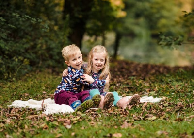Portrait of siblings hugging sat on a blanket at Dinton Pastures Country Park