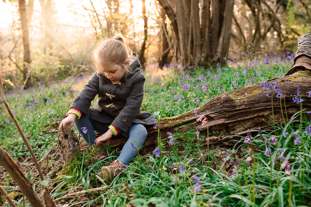Girl sat in bluebells at Harefield Copse near Wilder's Folly